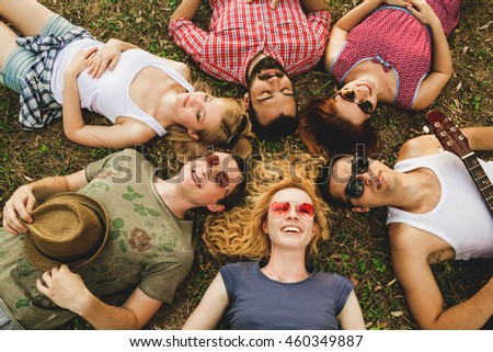 group of young happy friends lying on grass. top view.