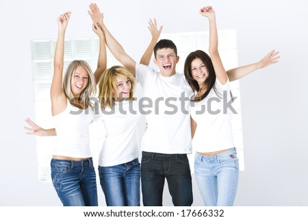 Group of young happy friends with upraised hands. They're looking at camera.  Front view.