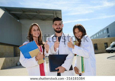 group of young happy medical students boys and girls together on a hospital university campus  - stock photo