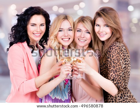 Group of young happy women have a party and drinking wine - indoors