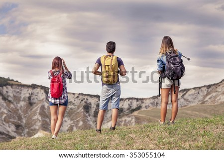 group of young hikers in the mountain looking at the horizon - stock photo