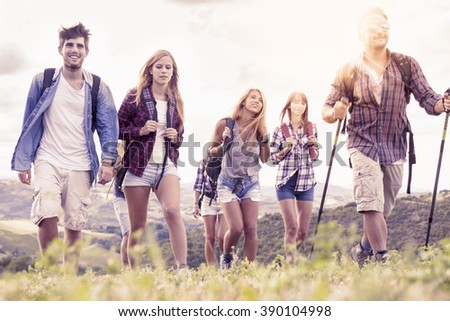 group of young hikers looks to the horizon over the mountain - stock photo