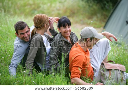 Group of young hikers sitting in the grass - stock photo