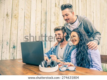 Group of young hipster people working with laptop - University students meeting in a wireless connected location to work with new technologies - Startup business and technologies concepts - stock photo