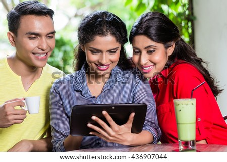 Group of young Indians looking at tablet computer while sitting in cafe - stock photo