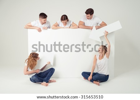 Group of Young Jolly Friends Looking and Pointing with Arrows the Blank Space of a Large Poster Against Off White Background in the Studio.