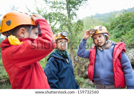 Group of young kids wearing helmet for cave exploration.  - stock photo