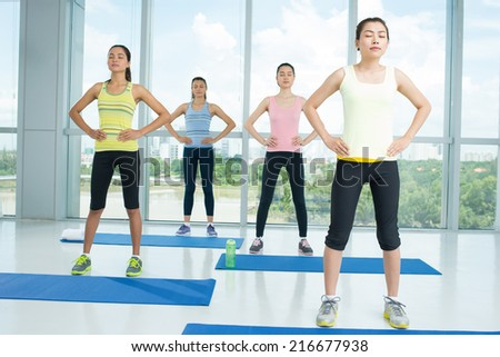 Group of young ladies doing relaxation exercise in the fitness club - stock photo