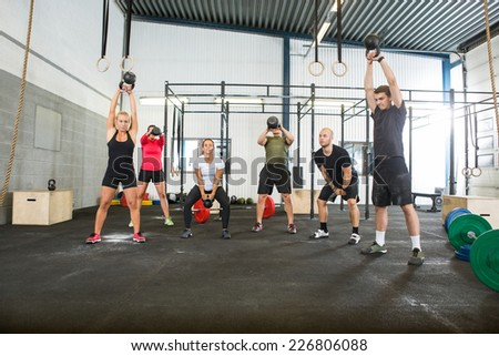 Group of young male and female athletes lifting kettlebells  - stock photo