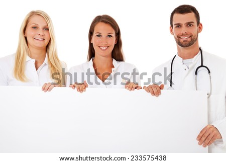 Group of young medical professionals standing behind placeholder. All on white background. - stock photo