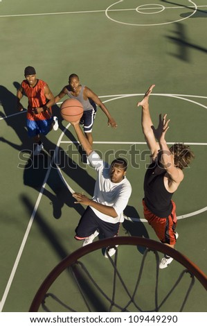 Group of young men playing basketball in court - stock photo