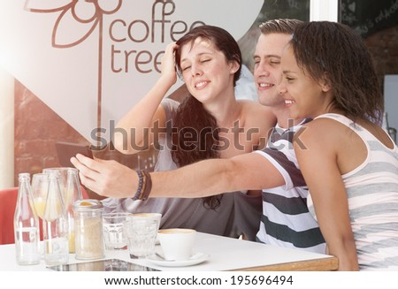 group of young mixed race people taking selfie  at coffee shop with mobile phone - stock photo