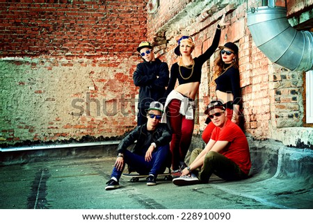 Group of young modern people posing together with fun. Urban lifestyle. Hip-hop generation.