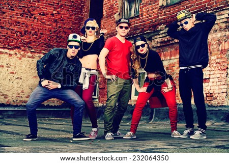 Group of young modern people posing together with fun. Urban lifestyle. Hip-hop generation. - stock photo