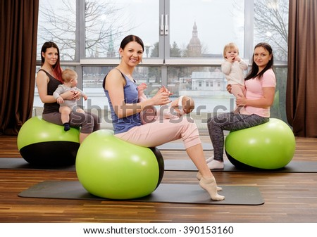 Group of young mothers and their babies doing yoga exercises on gymnastic balls at fitness studio. - stock photo
