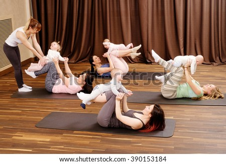 Group of young mothers and their babies doing yoga exercises on rugs at fitness studio. - stock photo