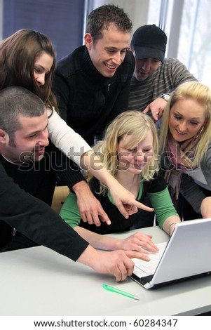 Group of young motivated students looking at a laptop computer - stock photo