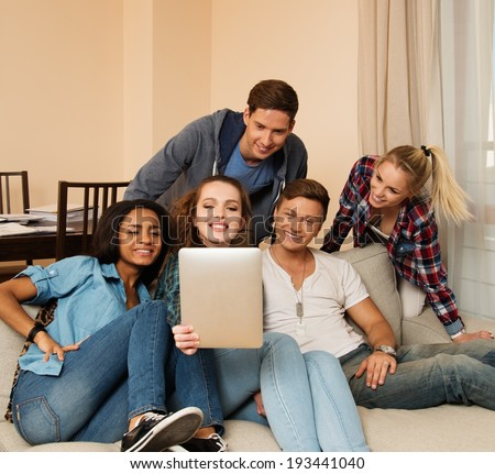 Group of young multi ethnic friends taking selfie in home interior  - stock photo