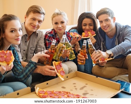 Group of young multi ethnic friends with pizza and bottles of drink celebrating in home interior