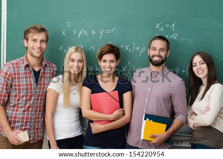 Group of young multiethnic college or university students standing in a row in front of a blackboard with cheerful friendly smiles looking at the camera - stock photo