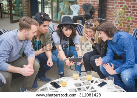 Group of young multiethnic friends sitting in a bar chatting to each other having fun using smartphone taking selfie - social network,technology, communication, technology concept  - stock photo