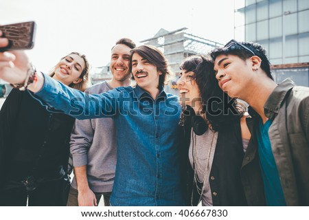 Group of young multiethnic friends taking a selfie with smart phone handhold , having fun - friendship, relaxing concept - stock photo