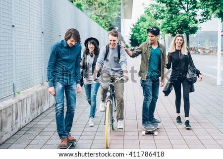Group of young multiethnic friends walking down the street holding skateboards in their hand, laughing and chatting each other - friendship, amusement, sportive concept - stock photo