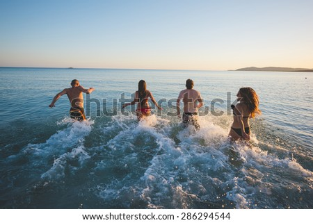 group of young multiethnic friends women and men at the beach in summertime - stock photo