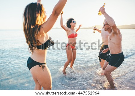 group of young multiethnic friends women and men at the beach in summertime jumping and dancing in back light - happiness, friendship, together concept