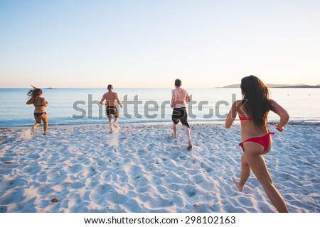 group of young multiethnic friends women and men at the beach in summertime running to the sea for taking a bath from back- race, childhood, carefreeness concept