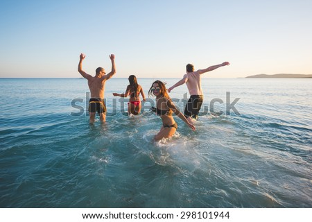 group of young multiethnic friends women and men at the beach in summertime taking a bath having fun in the sea - stock photo
