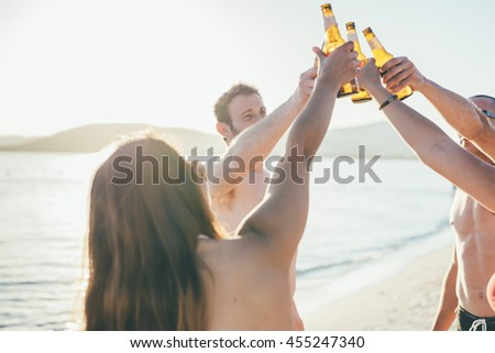 group of young multiethnic friends women and men at the beach in summertime toasting with some beers on the foreshore - friendship, relaxing, happy hour concepts