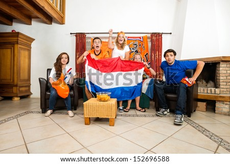 Group of young multiethnic soccer fans cheering while watching match at home - stock photo