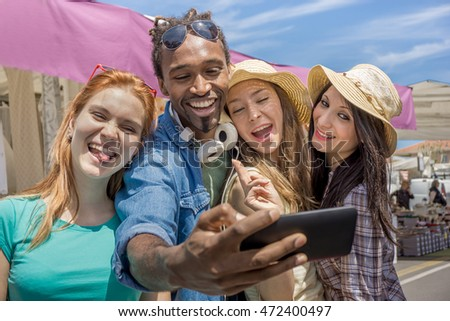 group of young multiracial friends, 3 girls and 1 guy taking selfie photo using smart phone out door - concept of happy college students on a trip having fun