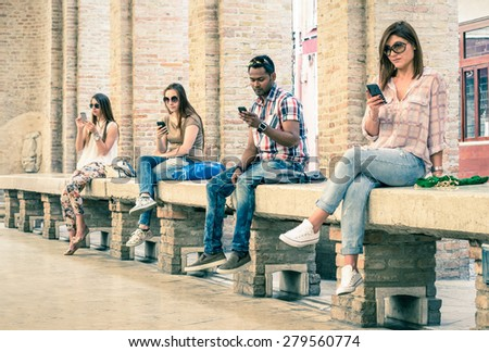 Group of young multiracial friends using smartphone with mutual disinterest towards each other - Technology addiction in actual lifestyle - Soft vintage filtered look with main focus on male person - stock photo