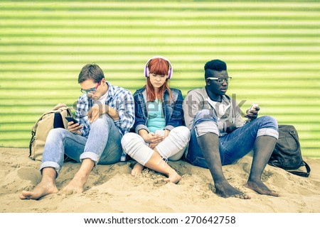 Group of young multiracial friends with smartphone and mutual disinterest towards each other - Social situation of new technology interaction in alienated lifestyle - Vintage nostalgic filtered look - stock photo