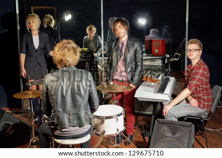 Group of young musicians in studio with mirror wall - stock photo