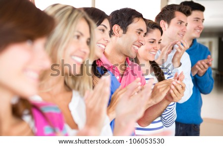 Group of young people applauding and looking very happy - stock photo