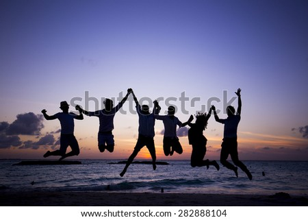 Group of young people at the beach at dusk. Silhouette group. - stock photo