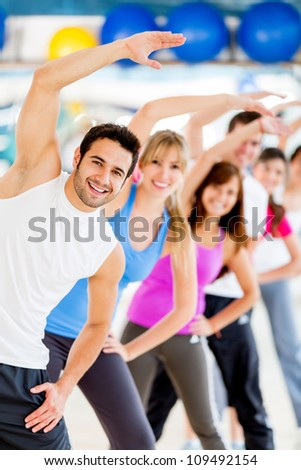 Group of young people at the gym stretching