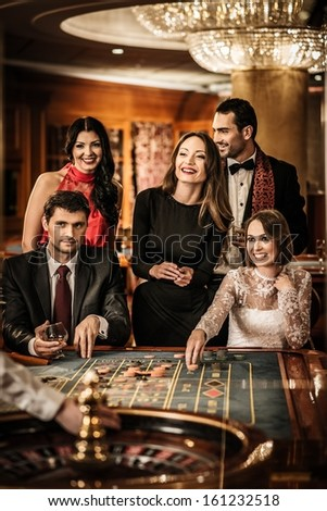 Group of young people behind roulette table in a casino - stock photo