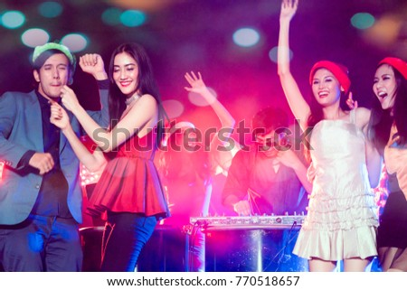 Group of young people celebrate new year party with spot light and fireworks in night party at club. selective focus on women in red dress. double exposure with bokeh background.