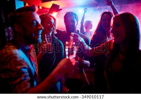 Group of young people celebrating with drinks in nightclub