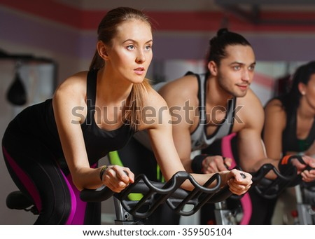 Group of young people cycling in class in gym - stock photo