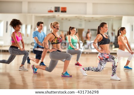 Group of young people doing exercises for legs and breech in gym - stock photo