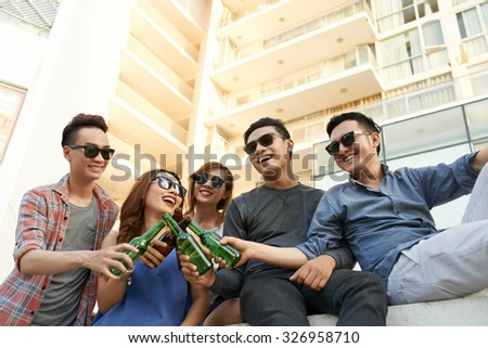 Group of young people drinking beer in the street - stock photo