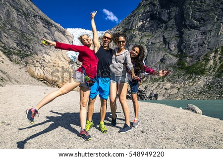 Group of young people enjoying the sunny day in national park next to the glacier Briksdaalsbreen, Norway
