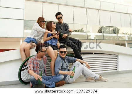 Group of young people having beer when resting outdoors