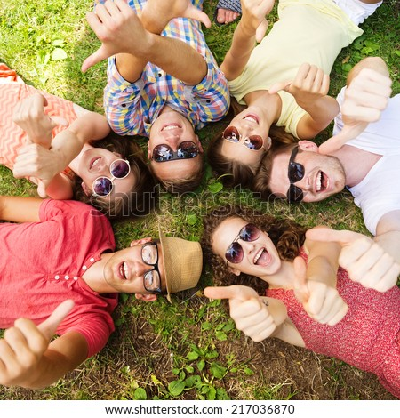 Group of young people having fun in park, lying on the grass - stock photo