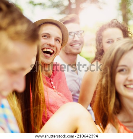 Group of young people having fun in park, sitting on the grass - stock photo